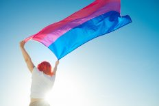 A Beautiful Low Angle Shot Of A Female Waving Red And Blue Flag